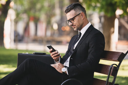 Portrait of a successful businessman dressed in formal clothes sitting outside on a bench and using mobile phone
